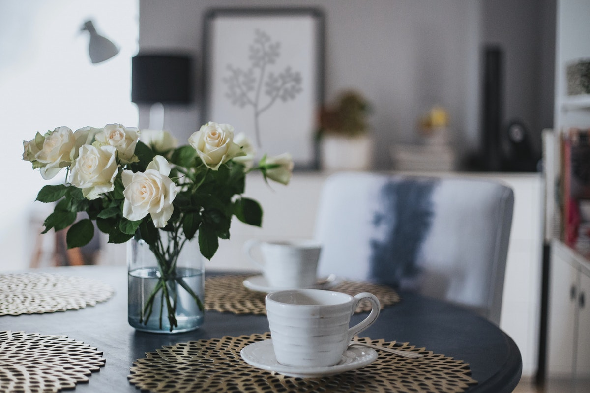New Start Staging - Life Begins After New Start - Dining Room, looking to open concept - living room - white cups and saucers on table with geometric patterned placemats, White roses in a vase in the center of the table.